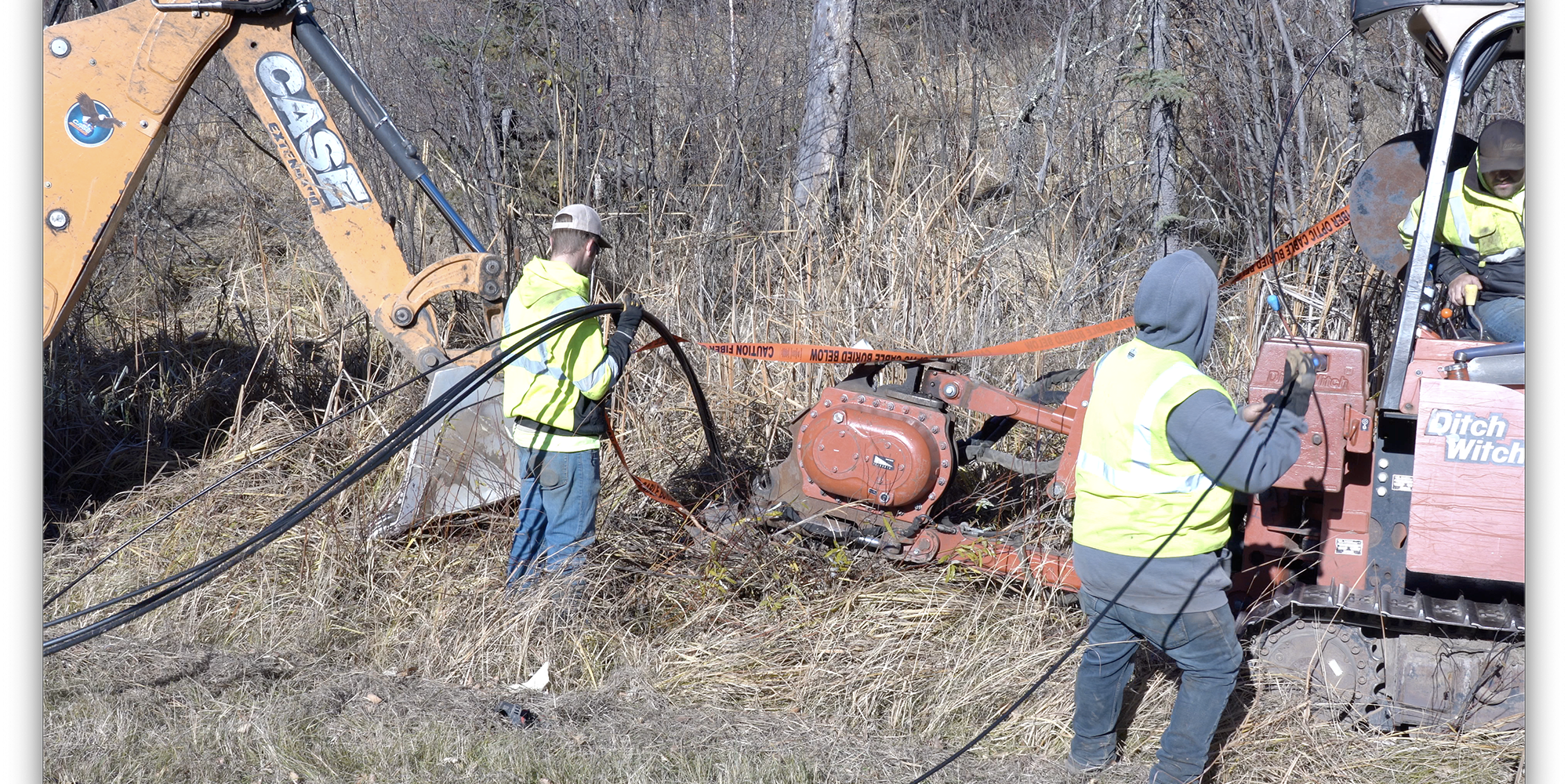 3 guys laying fiber optic cable with a backhoe and ditch witch.